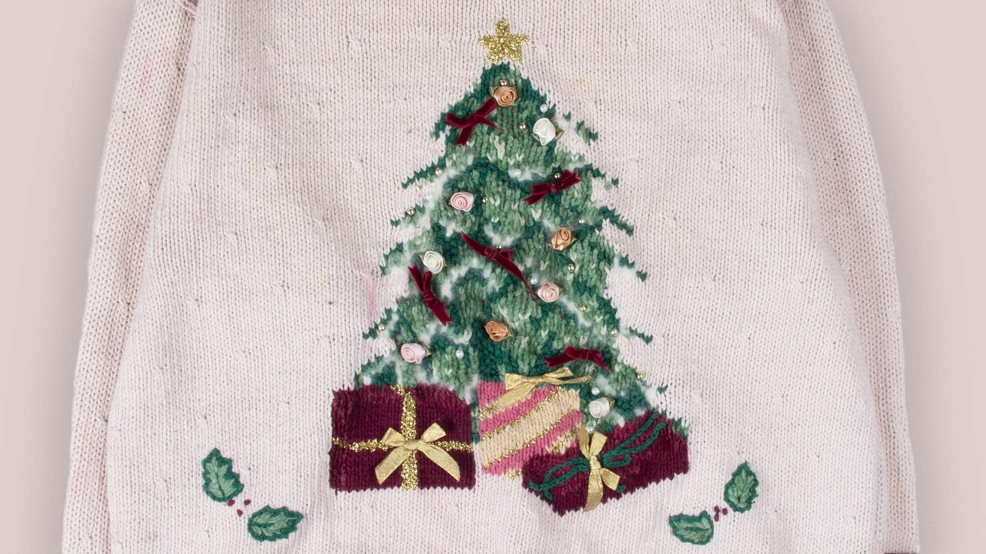 Ugly Christmas sweater featuring a Christmas tree adorned with fabric roses with presents all around it