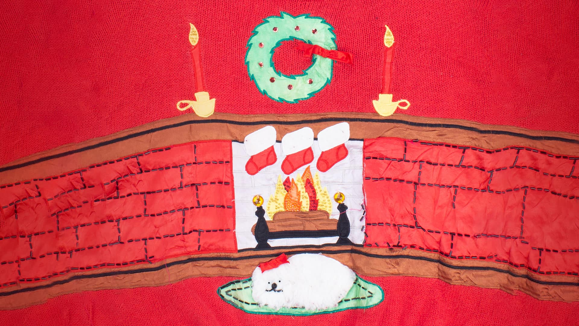 Ugly Christmas sweater featuring a fireplace with stockings hung and a wreath. There is a dog sitting in front of the fire with a red bow on its head.
