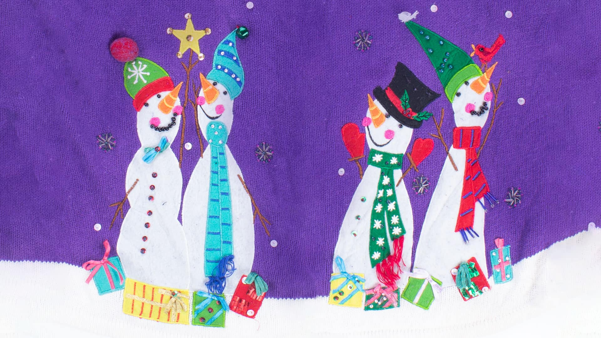 Ugly Christmas sweater featuring four snowmen all dressed up on a purple sweater background