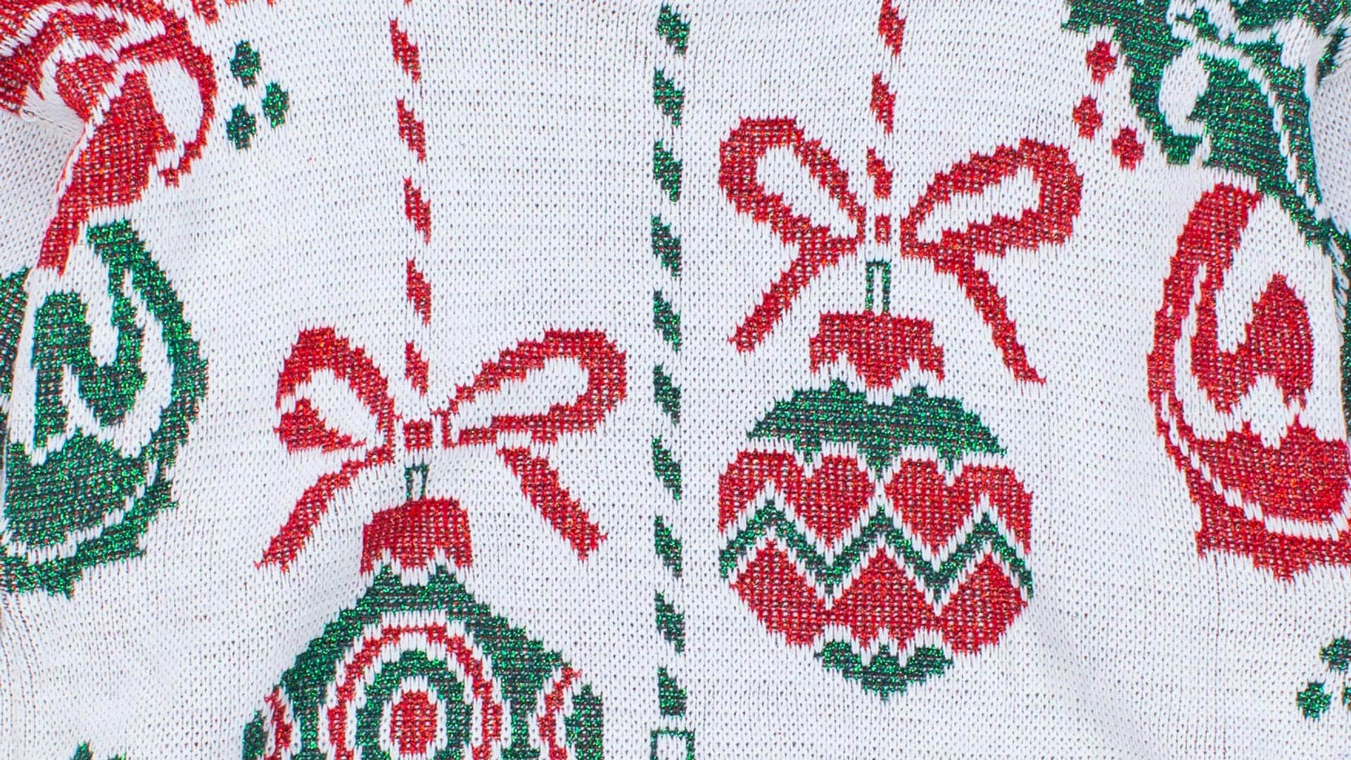 Ugly Christmas sweater featuring a close up of ornaments sewn with metallic thread.