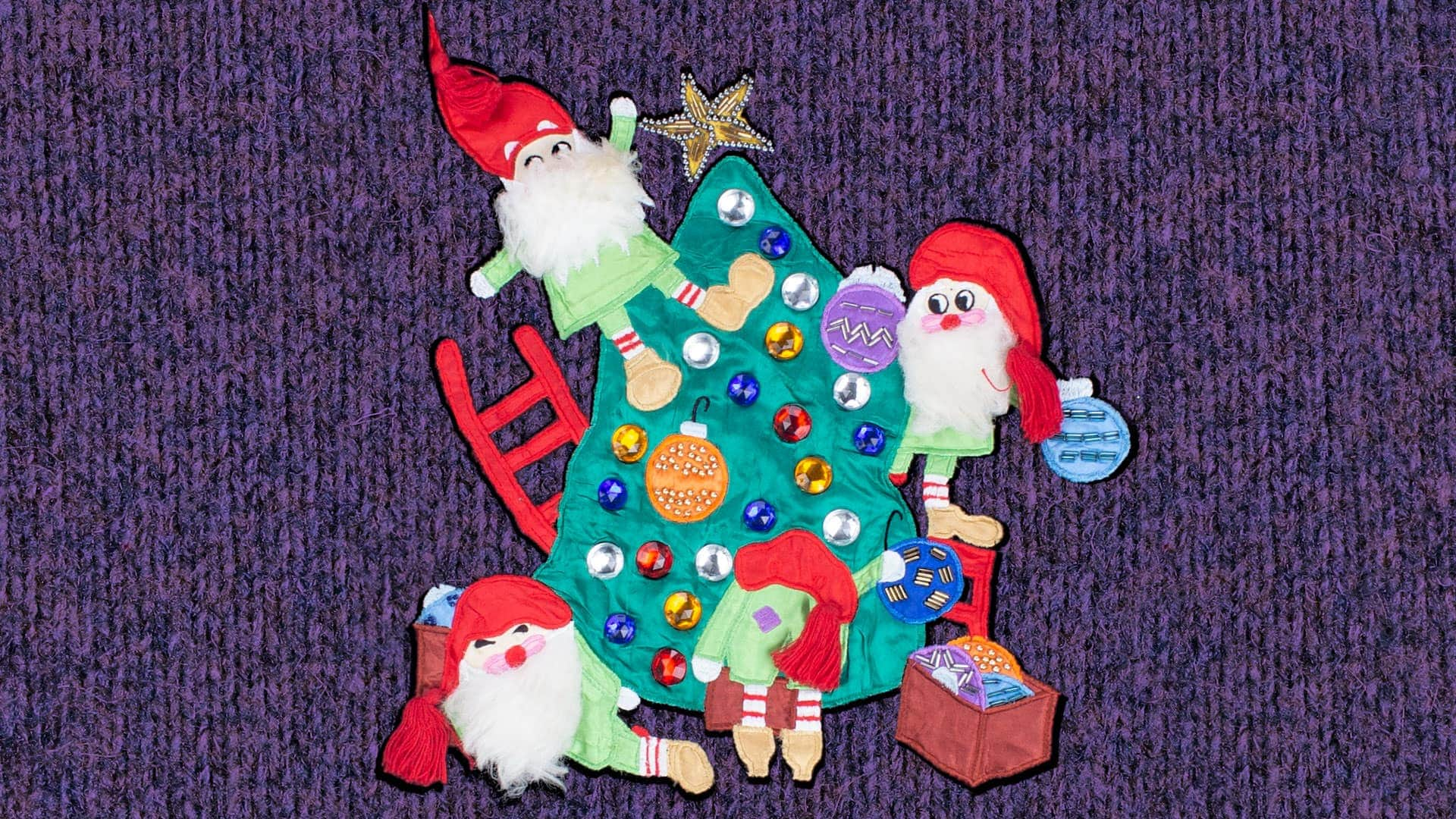 Ugly Christmas sweater featuring a group of elves decorating a Christmas tree. One of the elves is falling over.