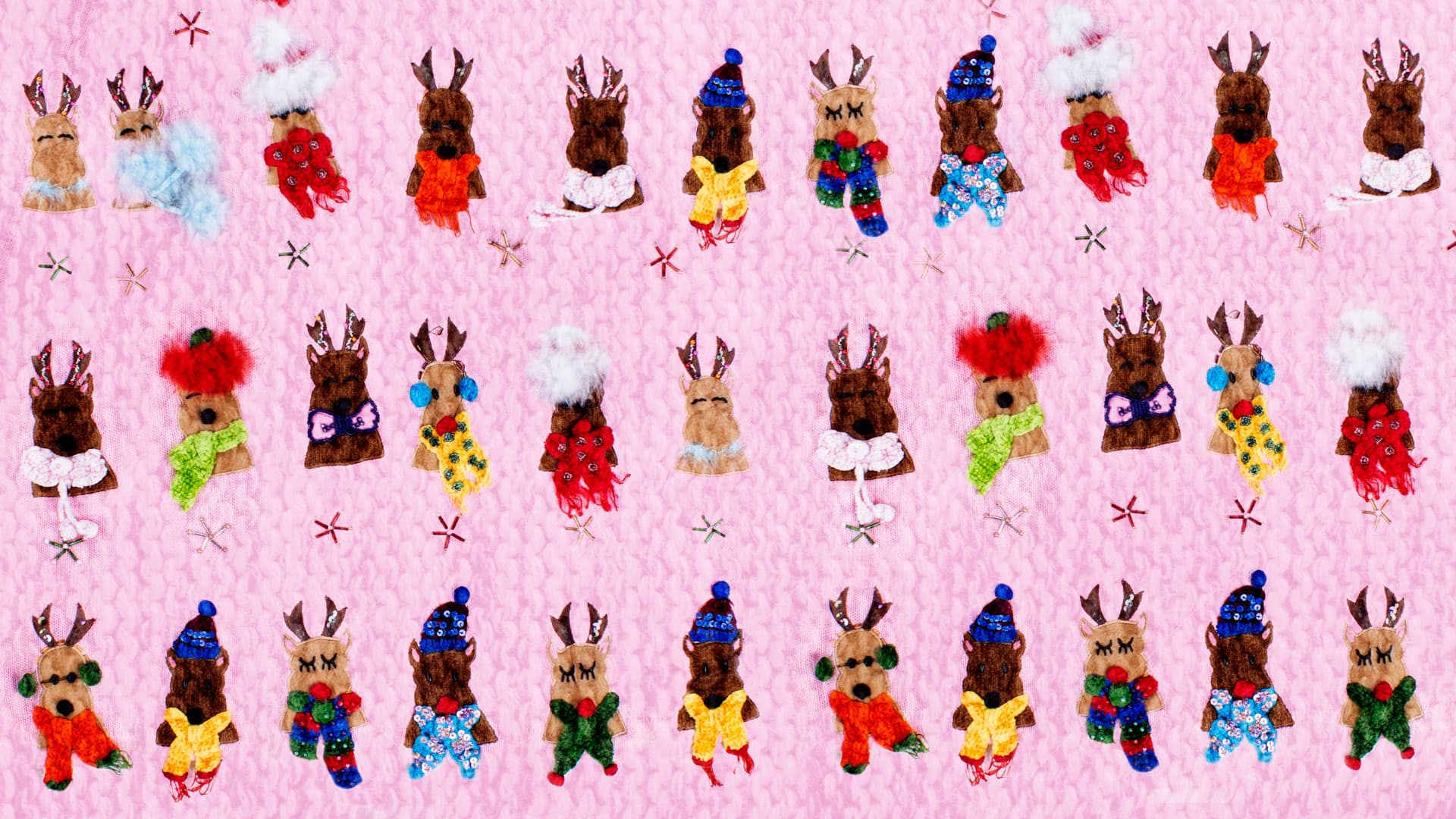 Ugly Christmas sweater featuring lots of reindeer wearing hats and scarves on a pink sweater background
