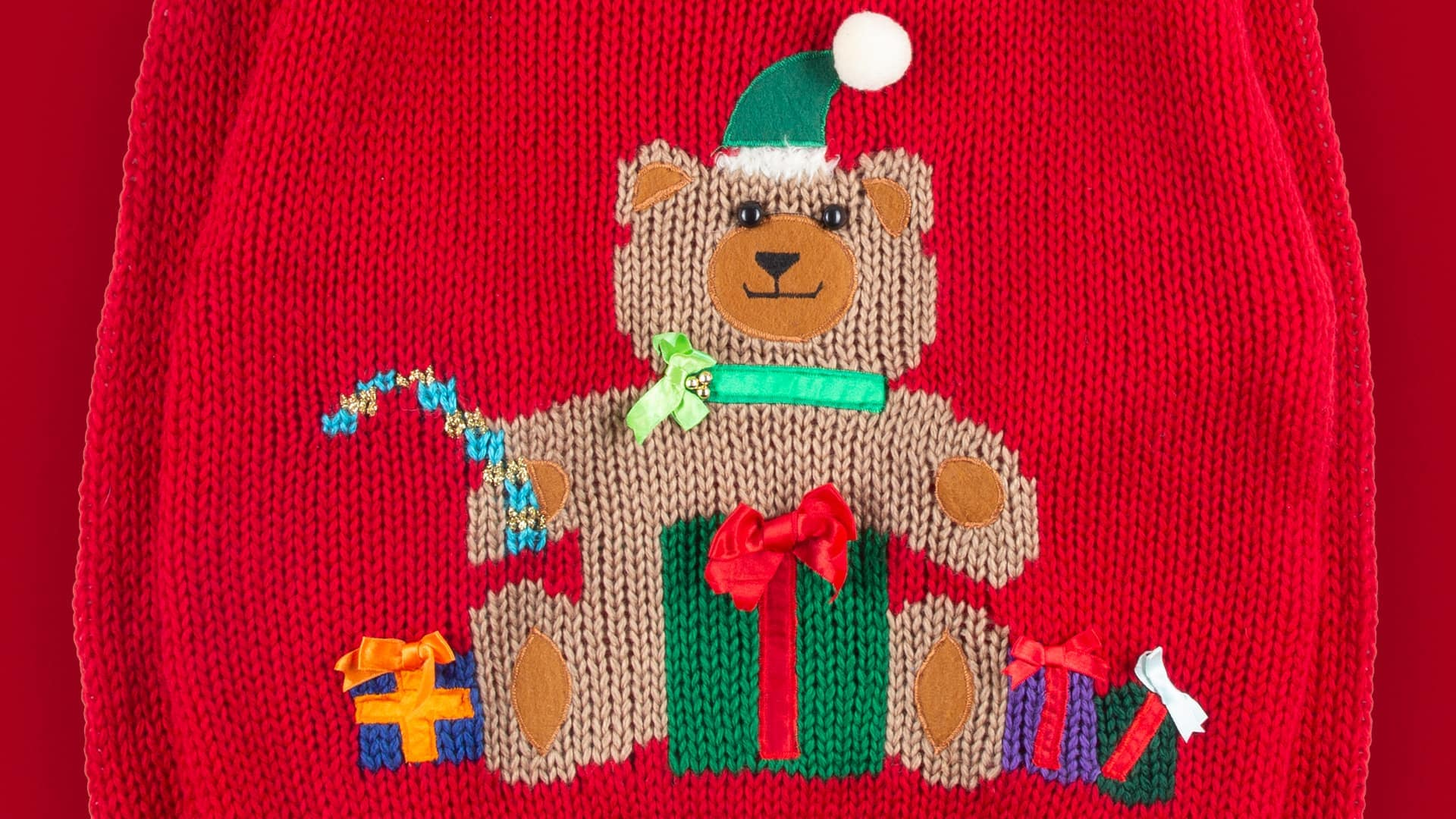 Ugly Christmas sweater featuring a teddy bear surrounded by presents.