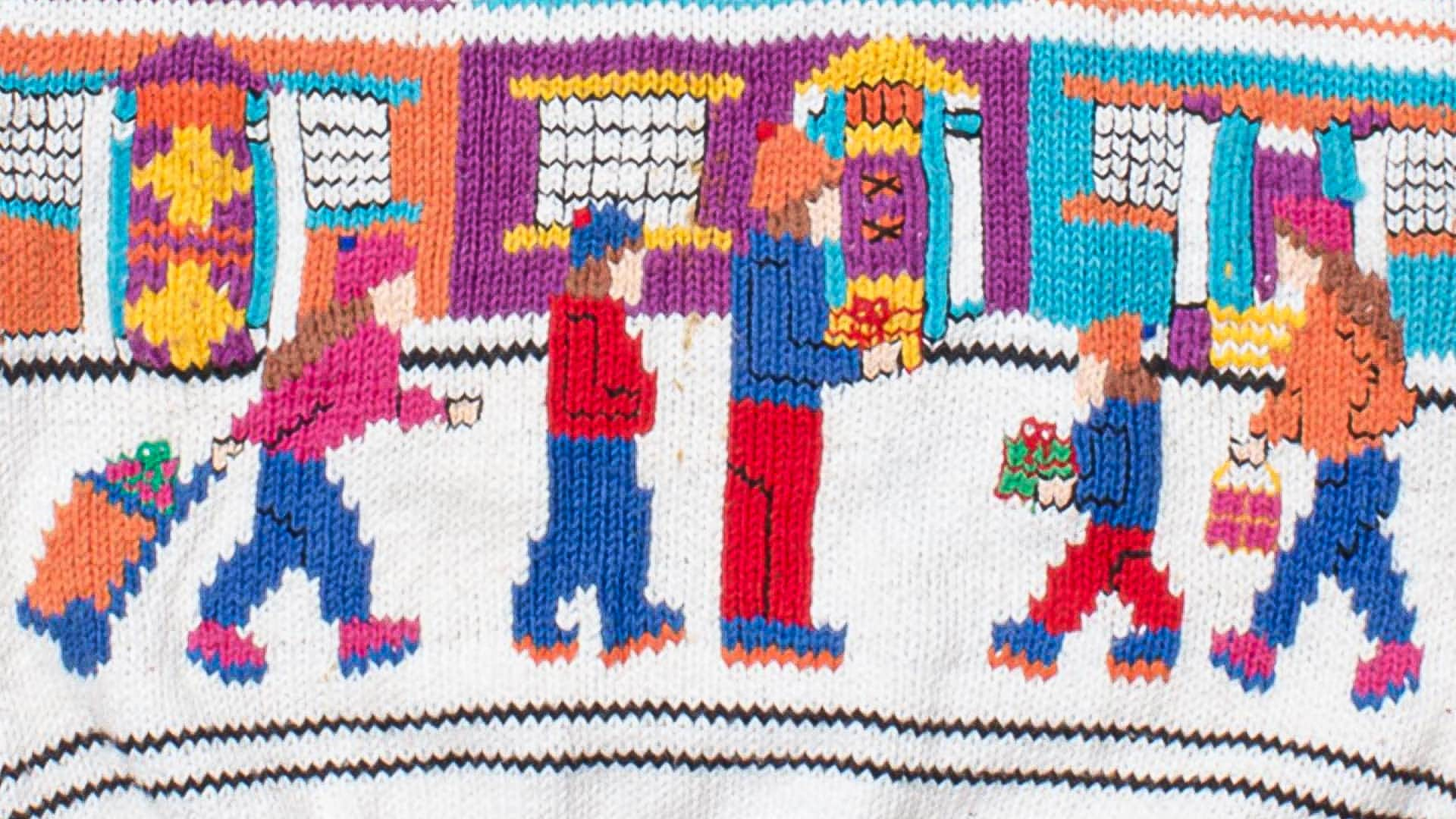 Ugly Christmas sweater featuring a group of people carrying Christmas presents down the street.