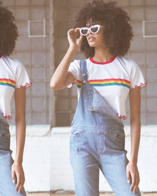 Woman with sunglasses poses in overalls and crop top.
