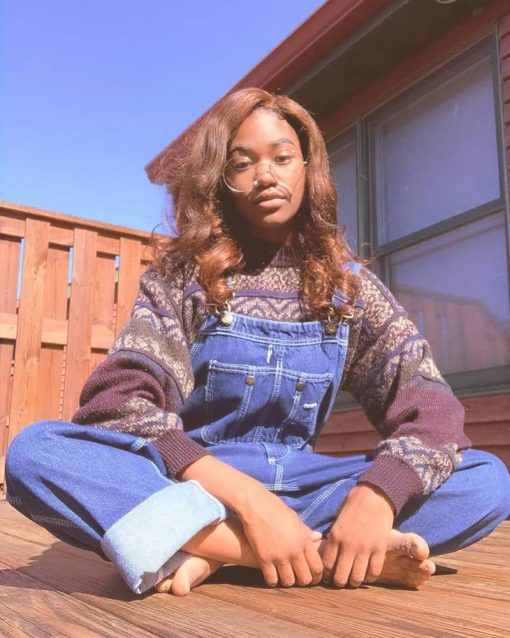 Woman sits on her porch wearing overalls and a sweater