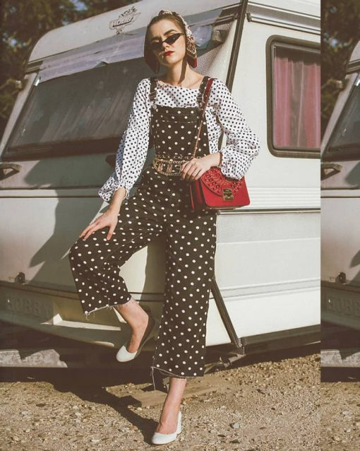 Woman wears polkadot print shirt under polkadot print overalls with bright red bag and many accessories.