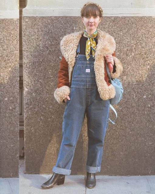 Woman wears a Y2K style jacket over overalls with a bandana around her neck.