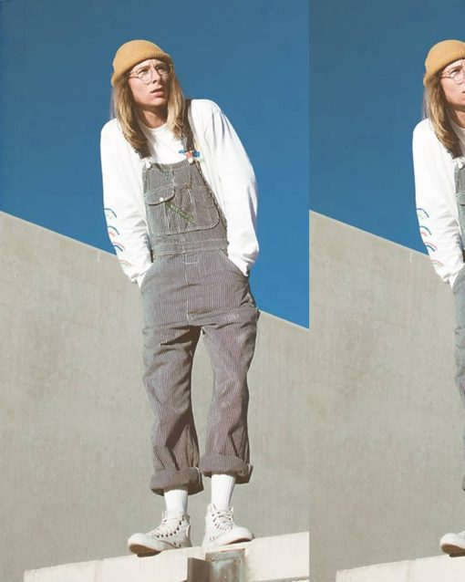 Man poses on the edge of a building with hands in the pockets of his corduroy overalls.