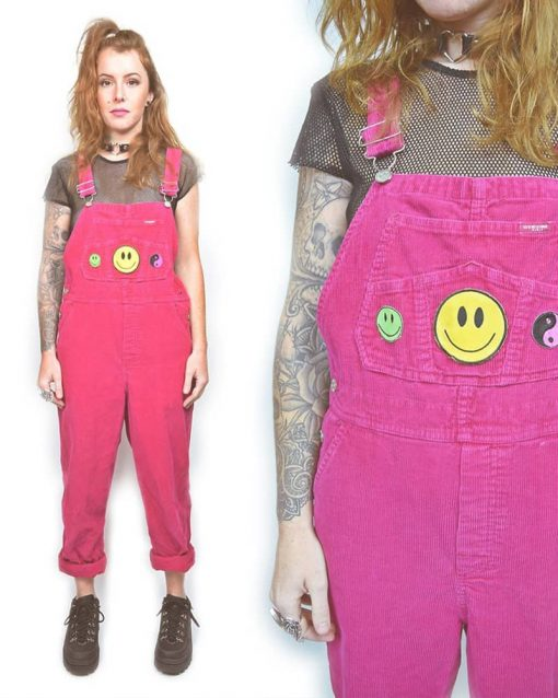 Woman wears neon pink overalls with smiley face and yin yang patches over a black mesh top.