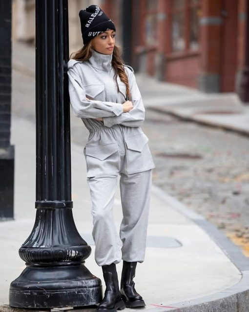 person leaving against a street light wearing a beanie and coveralls