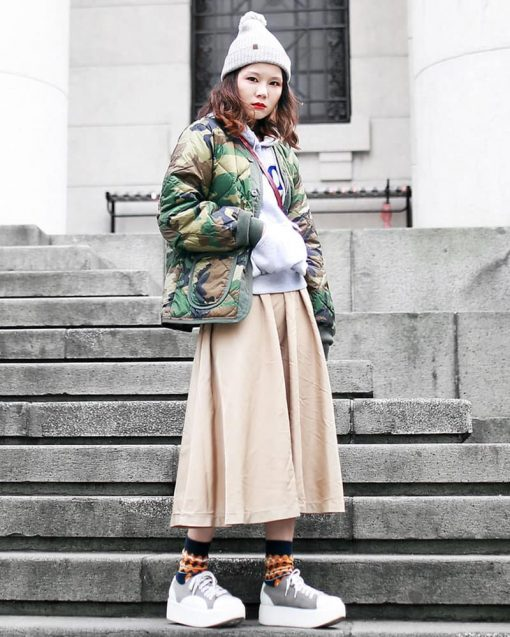woman standing on stairs wearing a beanie and long skirt