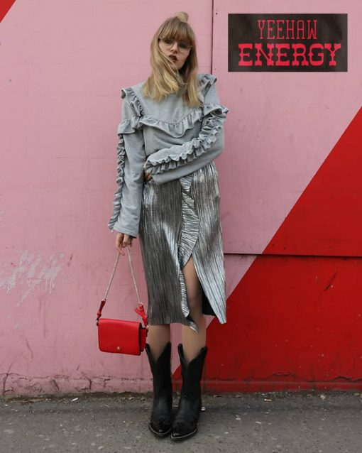 Woman poses against the wall wearing an extravagant outfit with cowboy boots.