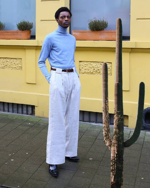man poses on the sidewalk wearing baggy pants and cowboy boots.
