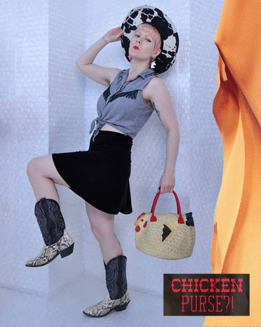 woman poses with leg in the air, wearing cow print cowboy hat, firing top, chicken purse, and cowboy boots.