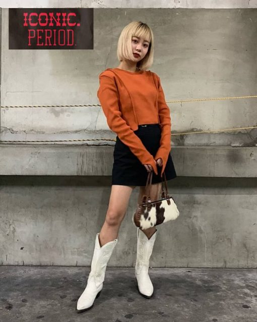 woman poses in parking garage in cowboy boots.