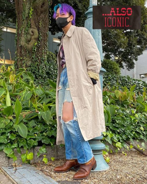 man with purple hair wears trench coat, distressed jeans, and boots.