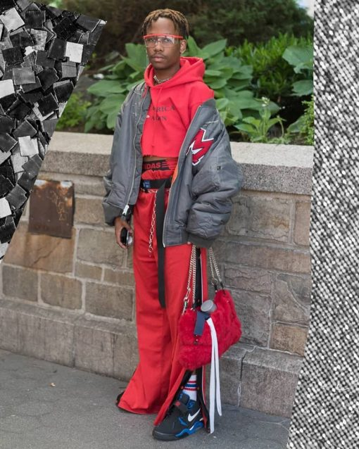 Person in New York stands on the sidewalk in many layers, including a cropped red hoodie.