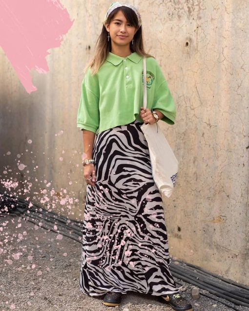 Woman in New York poses in a green cropped polo shirt and long zebra print skirt.