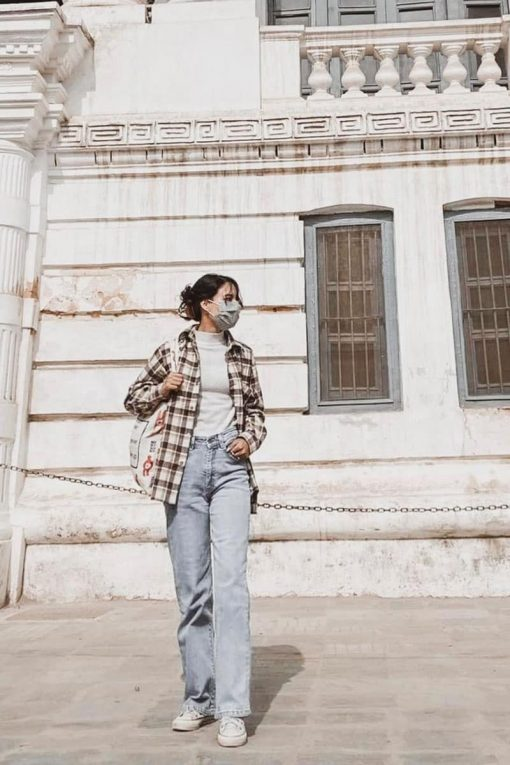 woman wearing lightwash jeans, a flannel shirt, and a face mask