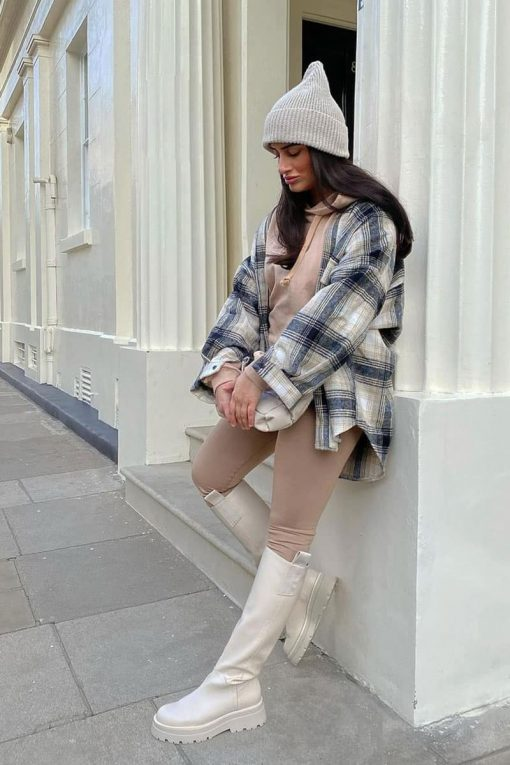 woman wearing tall boots and a large flannel shirt