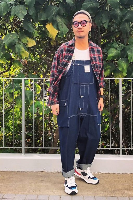 man wearing a flannel shirt over overalls