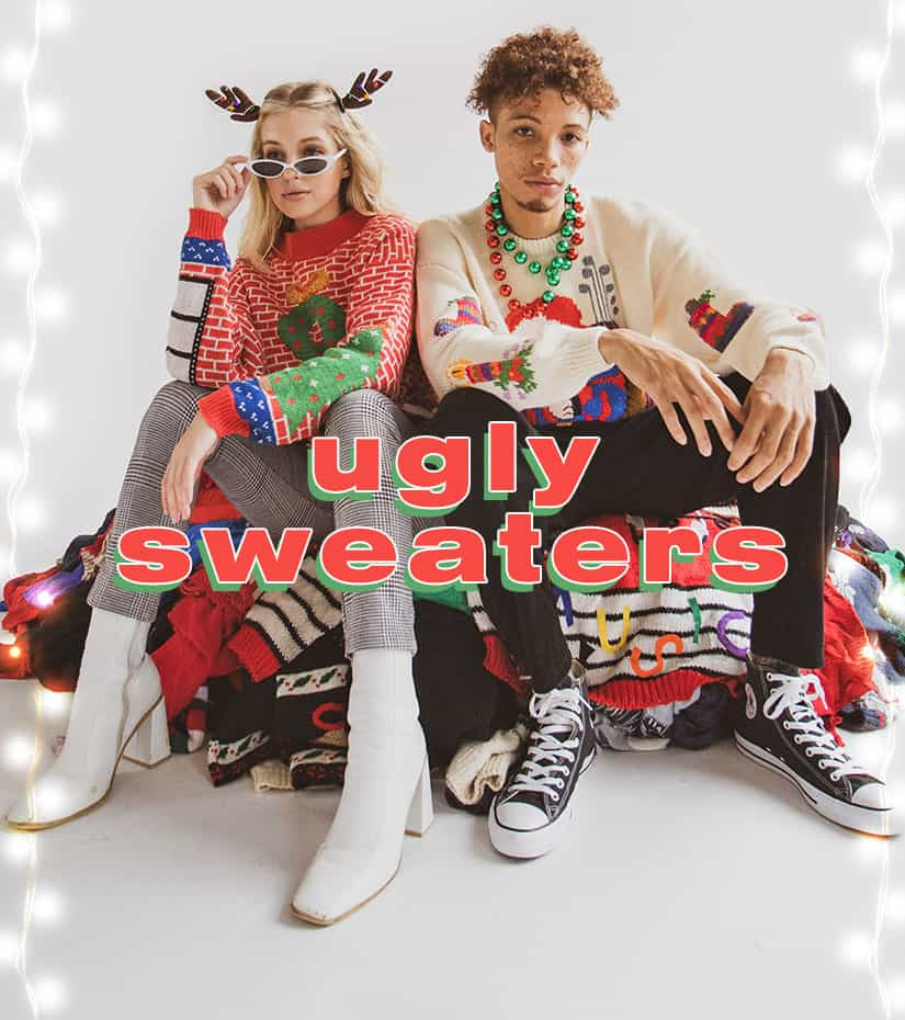 a girl and a guy wearing ugly christmas sweaters sitting on top of a pile of ugly sweaters