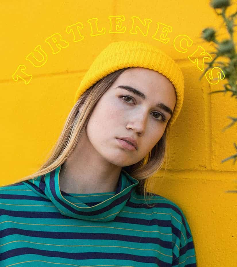 model wearing a vintage turtleneck leaning against a yellow wall